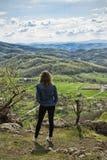 Een wandelend meisje zit op de rand van de klip en het bekijken de vallei en de bergen Stock Foto's