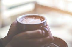 Een warme kop van koffie is op hand stock fotografie