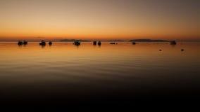 Een warme zonsondergang op een kalm water, met Eilanden op de achtergrond Stock Afbeelding