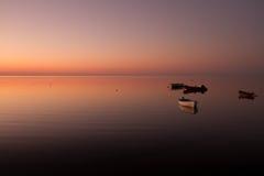 Een warme zonsondergang op een kalm water, met Eilanden op de achtergrond Stock Afbeeldingen