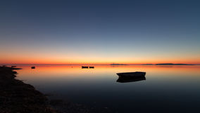Een warme zonsondergang op een kalm water, met Eilanden op de achtergrond Stock Foto