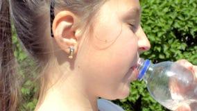 Een water van meisjes dicht updrinks van een plastic fles stock videobeelden