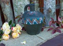 een waterkruik en een boeket van rozen Royalty-vrije Stock Foto's
