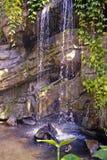 Een waterval die over steen stroomt stock afbeelding
