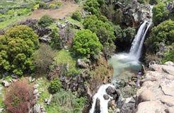 Een waterval en een stroom stromen tussen de rotsen stock foto's