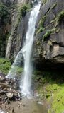 Een waterval op een rots en mensen stock afbeeldingen