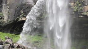 Een waterval over een grot in een rots stock videobeelden