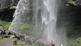 Een waterval over een grothol in een rots en mensen stock videobeelden