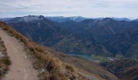 Een weg die tot de bovenkant van Ben Lomond dichtbij Queenstown in Nieuw Zeeland, bergen op de achtergrond leiden stock afbeeldingen