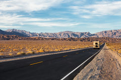 Een weg loopt in het Nationale Park van de Doodsvallei, Californië, de V.S. Motorhome op de weg Stock Afbeeldingen