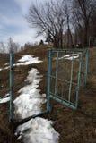 Een weg met smeltende sneeuw die door de poort overgaan en weg de afstand tegenkomen stock foto