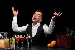 Een weggegaane barman bij een barteller, sinaasappelen, citroen, een schudbeker, de glazen van Margarita op een zwarte achtergron Stock Foto