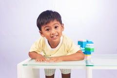 Een weinig het Aziatische jongen spelen met kleurrijke plastic blokken Stock Foto