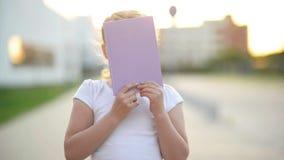 Een weinig Jong geitje het Spelen met een Boek Zij heeft heel wat Pret Het Boek zal geeft aan haar heel wat Kennis Zij kijkt stock videobeelden