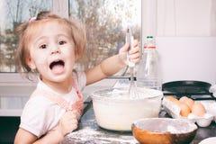 Een weinig leuk meisje die het deeg in de keuken thuis voorbereiden stock afbeeldingen