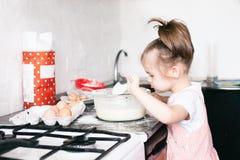 Een weinig leuk meisje die het deeg in de keuken thuis voorbereiden stock afbeelding