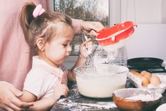 Een weinig leuk meisje en haar moeder die het deeg in de keuken thuis voorbereiden royalty-vrije stock afbeeldingen