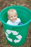 Een weinig leuke blonde jongenszitting in een groene recyclingsbak op een vage achtergrond van de parkgrond Het concept van de ec Stock Foto's