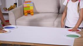 Een weinig leuke gelukkige grappige kind het schilderen kleur handprints op het witte blad van document Langzame Motie stock videobeelden