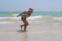 Een weinig leuke jongenslooppas langs het strand en de spelen stock foto's