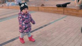 Een weinig zoet meisje in een kleurrijk roze jasje dat mamma verzoekt dichtbij een speelplaats in een park op de rand van het bos stock footage