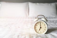 Een wekker die op een witte matras wordt geplaatst royalty-vrije stock afbeelding