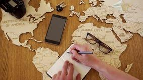Een wereldkaart van hout wordt gemaakt dat Een mens schrijft een plan van zijn reizen in een notitieboekje Voorbereiding voor rei stock video