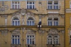 Een werkende mens die de muur van een mooi huis schilderen Royalty-vrije Stock Afbeelding