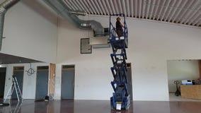 Een werkende mens op het bevestigende plafond van de schaarlift Bouwwerkzaamheidconcept stock video