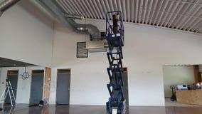 Een werkende mens op het bevestigende plafond van de schaarlift Bouwwerkzaamheidconcept stock footage