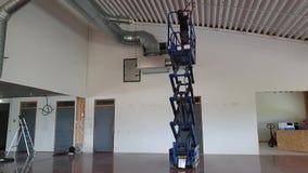Een werkende mens op het bevestigende plafond van de schaarlift Bouwwerkzaamheidconcept stock videobeelden
