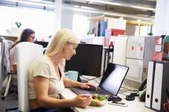 Een werkende vrouw die lunch eten bij haar bureau stock foto's