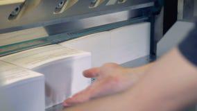 Een werknemer draait rond stapels van document de waarvan oneven die randen door een industriële snijder worden afgesneden worden stock video