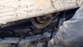 Een werknemer herstelt een bulldozer Reparatie van zwaar bouwmateriaal bij de bouwwerf stock footage