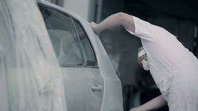 Een werknemer maakt een autobumper schoon stock videobeelden