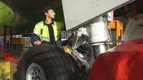 Een werktuigkundige inspecteert de voorvliegtuigen van de stutpassagier 4K stock footage