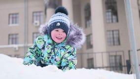 Een werpt de kleine kindspelen op een sneeuwberg, sneeuw en lacht Zonnige ijzige dag Pret en spelen in de verse lucht stock video