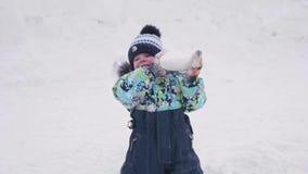 Een werpt de kleine kindspelen op een sneeuwberg, sneeuw en lacht Zonnige ijzige dag Pret en spelen in de verse lucht stock footage