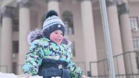 Een werpt de kleine kindspelen op een sneeuwberg, sneeuw en lacht Zonnige ijzige dag Pret en spelen in de verse lucht stock videobeelden