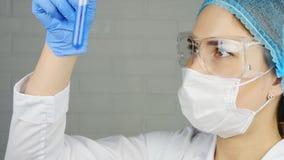 Een wetenschapper bekijkt een steekproef van een chemisch product in een laboratorium stock video