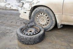 Een wiel met een compressor dichtbij een oude auto op een vuile weg stock afbeelding