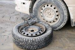Een wiel met een compressor dichtbij een witte auto op een vuile weg stock afbeelding