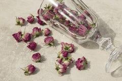 Een wijnglas met droge rozen stock foto