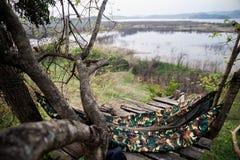 Een wildernishangmat hangt tussen bomen op de houten steiger Stock Foto's