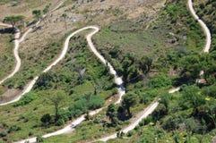 Een windende weg onderaan een berg in westelijk Sicilië Stock Fotografie
