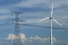 Een windturbine dicht bij een elektrische pyloon Royalty-vrije Stock Afbeeldingen