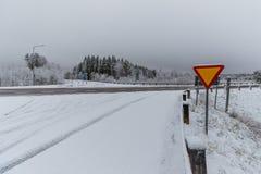 Een winterse dwarsweg met een teken Stock Afbeelding
