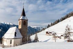 Een wintertijdmening van een kleine kerk met een lange torenspits Stock Foto