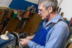 Een wit bejaarde met glazen werkt bij een draaibank in een timmerwerkworkshop Het concept het verhogen van de pensioneringsleefti stock foto's