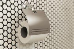 Een wit broodje die van zacht toiletpapier keurig op een moderne chroomhouder hangen op een lichte badkamersmuur Sluit omhoog Stock Foto's